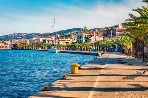 A palm-lined pedestrian promenade stretches round the harbour front in Argostoli, Kefalonia