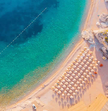 An aerial view of golden sands and turquoise waters along the Budva Riviera