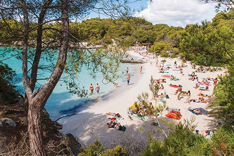 Powder-white sands are surrounded by trees at Cala en Turqueta