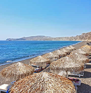 A beach in Santorini with sunloungers and parasols
