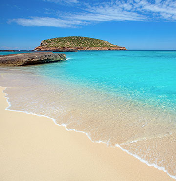 Golden sands and blue seas of Cala Conte beach in Ibiza