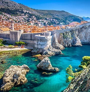 The Old Town city walls of Dubrovnik surrounded by the azure waters of the Adriatic Sea