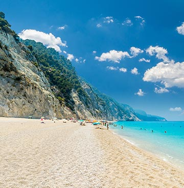 Powder-white sands, brilliant blue waters and towering limestone cliffs on a beach in Lefkas, Greece