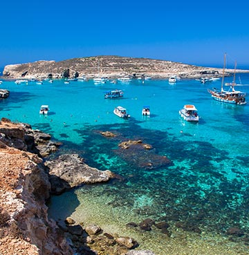 Comino's beautiful blue lagoon. Tour boats and private charters are dotted throughout the crystal clear waters.