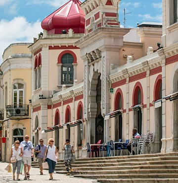 Pedestrians carrying shopping in the streets of Loule, walking by a beautiful building with a red domed roof
