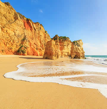 A gentle wave breaks against the golden sands of a beach in the Algarve