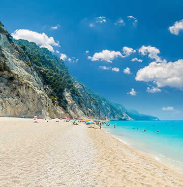 Soaring limestone cliffs frame a white, sandy beach on the Greek Island of Lefkas