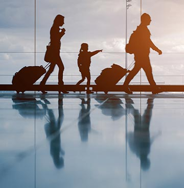 Silhouettes of a young family making their way through an airport against a glass window backdrop