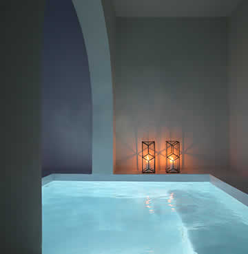 A candlelit, private plunge pool on a romantic evening in Santorini