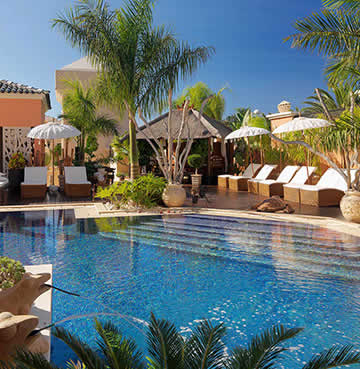 Luxury pool area shaded by palm trees and lined with sunloungers at a Holiday Resort in Tenerife
