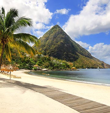 The pristine Sugar Beach with perfect white-sands, calm Caribbean waters and swaying palm trees. Gros Piton sits majestically in the background.