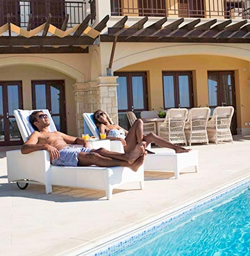 A young couple relax on sunloungers by the pool