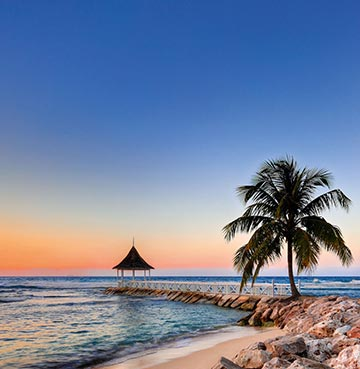 The sun sets at the Half Moon Resort in Jamaica. A tranquil beach, lone palm tree and beach side walkway make for a romantic evening stroll.