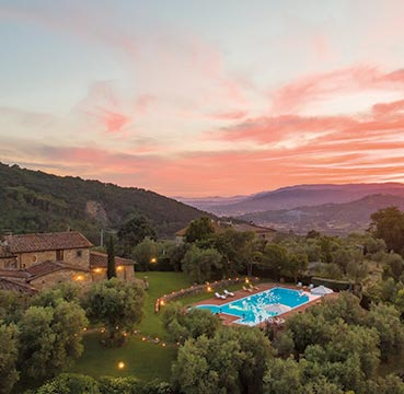 The luxurious Villa Dell Angelo wedding venue nestled in the beautiful Tuscan countryside. The sky is coloured with perfect pinks and purples as the sun sets in the distance.