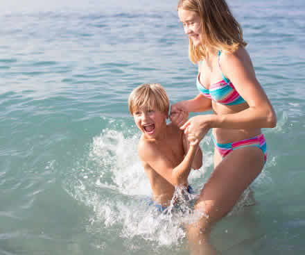 Kids playing in the sea on holiday in Europe