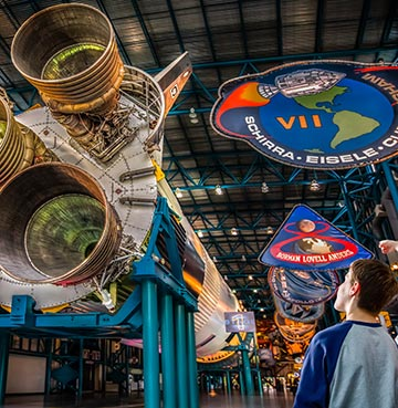 A young family staring up in wonder at a suspended rocket ship in a huge hanger at Kennedy Space Center