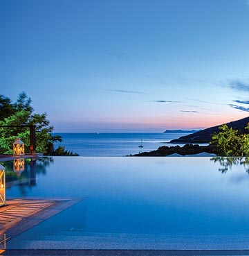 A luxury infinity pool in Epirus at sunset. Traditional lanterns light the decking area. Steps graduate in to the front of the pool for easy access. A panoramic view of the Greek coastline can be seen from the pool.
