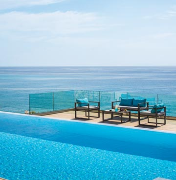 Modern infinity pool with seating area to the side boasts panoramic views of the ocean