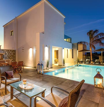 Contemporary whitewashed villa and grounds. Surrounded by large pool, sunloungers, palm trees and outdoor dining area.