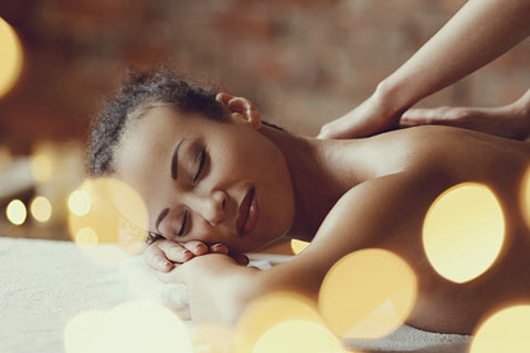 A young woman on a massage table receiving a back massage in a modern spa