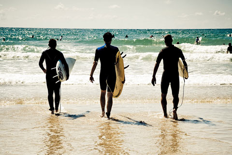 Three surfers with surf boards about to step into the waves of the Silver Coast, Portugal