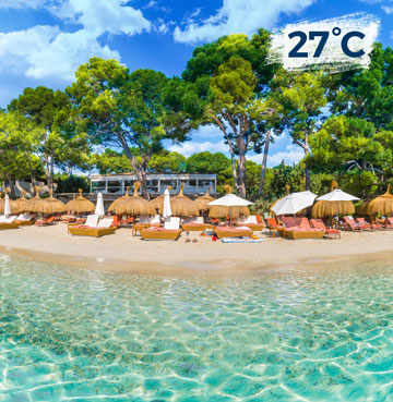 Crystalline waters lap gently against a beach lined with sunloungers and umbrellas