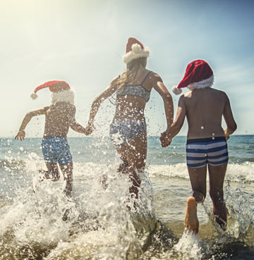 Family running into the sea wearing Christmas hats