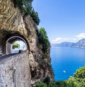 A tunnel is built into the cliff along the famous Amalfi Coast. The road is made up of hairpin bends and unbeatable panoramic views.