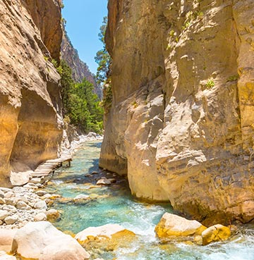 Crystal clear river flowing through Samaria Gorge. Brilliant blue skies can be seen in the background.