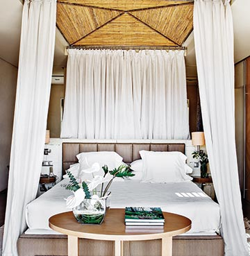 A luxury four poster bed hung with white linen and covered in a plush white duvet and pillows