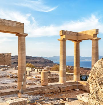The Acropolis of Lindos. Ancient ruins and towering columns are set against a rugged, mountainous backdrop.