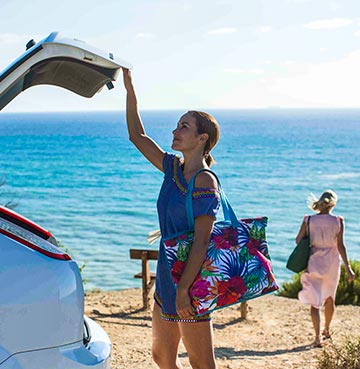 Woman closes the boot of her hire car, having just arrived at a beautiful coastal location