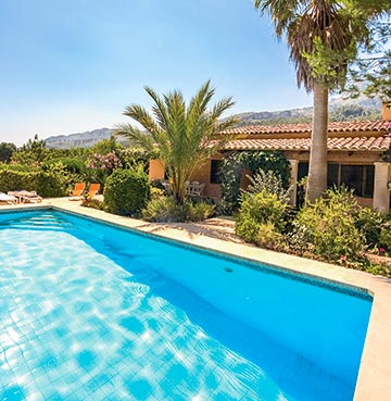 Blue skies sit over a traditional villa with private pool and beautiful gardens