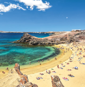 Holidaymakers enjoy azure waters and golden sands at Papagayo Beach