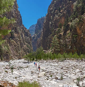 Soaring cliffs of Samaria Gorge with three hikers making their way through the rocky terrain