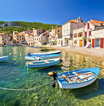 Boats on the crystal clear waters of Komiza, Vis, Croatia