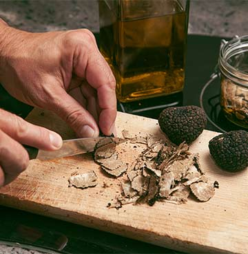 Preparing Umbrian truffles with oil on a chopping board