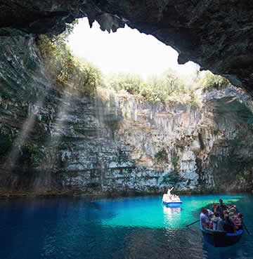 Golden light shines in through the collapsed ceiling of Melissani Cave, Kefalonia