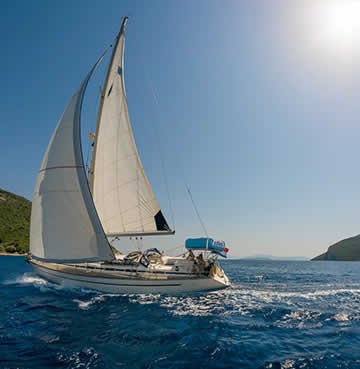 A small white yacht making waves across the Ionian Sea