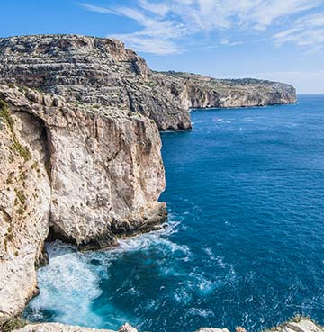 Rugged Dingli cliffs towering above wild waters and crashing waves