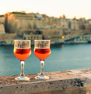 Two glasses of Maltese wine perched on top of a wall at sunset, looking out across Valletta harbour
