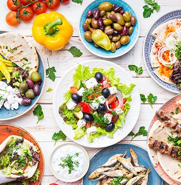 A bird's eye view of a dinner spread covered in colourful and fresh meze dishes