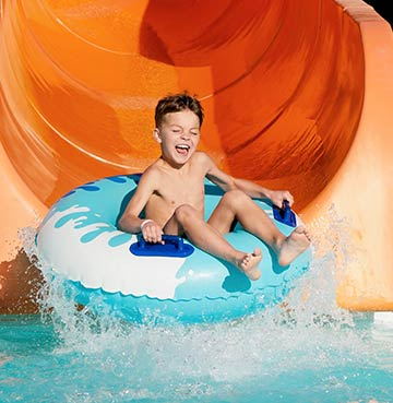 Young boy in a rubber ring on a waterpark slide