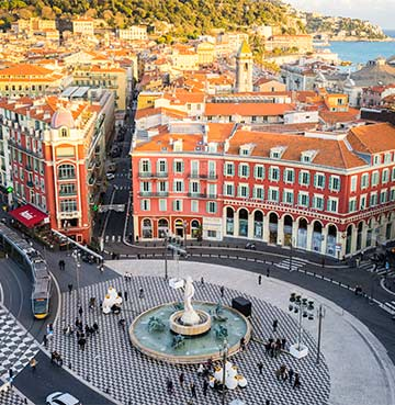 Colorful buildings and fountain in a square in Nice, South of France