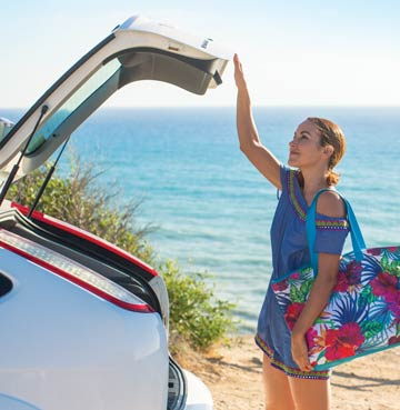 Woman closing boot of hire car on villa holiday