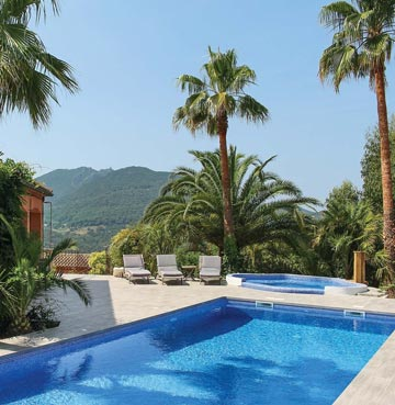 View of pool, palm trees and countryside in Villa La Mastaniere, Cote d'Azur