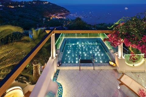 A modern, chic infinity pool and villa patio overlook the iconic Amalfi Coast at night