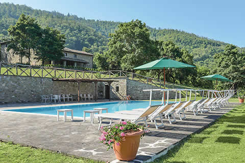 A luxury pool area with sunloungers and parasols in the heart of the Tuscan countryside