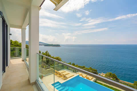 A modern balcony and infinity pool overlook the bright blue Adriatic Sea in the Dubrovnik Region of Croatia