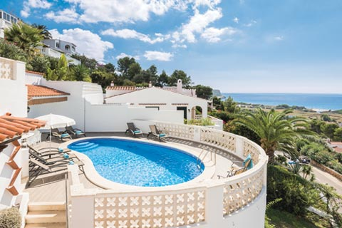 A whitewashed, traditional villa in Menorca overlooks rolling countryside and out to sea